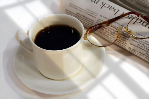 Table with morning newspaper, coffee, and reading glasses